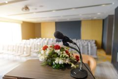 Microphone on the podium over blurred of empty seminar or conference room background. Microphone on the podium over abstract blurred of empty seminar or stock photo