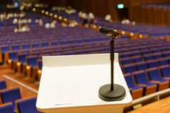 Microphone on the podium in conference hall. Microphone on the podium in seminar or conference hall royalty free stock photography