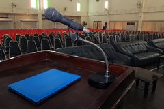 The microphone on podium stand at the center of the room to prep. The microphone is located on podium stand at the center of the room is covered with a red royalty free stock image
