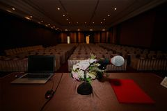 The microphone on podium stand at the center of the room to prep. The microphone is located on podium stand at the center of the room is covered with a red royalty free stock photography