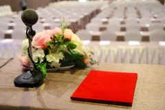 The microphone on podium stand at the center of the room to prep. The microphone is located on podium stand at the center of the room is covered with a red royalty free stock images