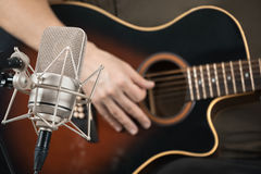 Microphone recording an acoustic guitar played by hand. Front view Stock Image