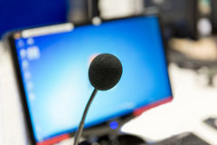 Microphone at recording studio or radio station. Technology, electronics and audio equipment concept - close up of microphone and computer monitor at recording royalty free stock images