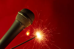 Microphone on red background and sparkler Stock Photography