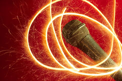 Microphone on red background and sparkler. Studio microphone on red background and sparkler sparkling around Stock Images