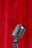 Microphone before a red curtain. Silver microphone in front of a red curtain Royalty Free Stock Images
