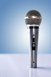 Microphone with reflections standing on white table and blue bac Stock Photos