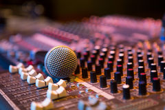 Microphone resting on a sound console Stock Images