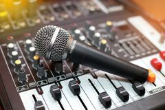 Microphone resting on a sound mixer. Royalty Free Stock Image