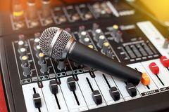 Microphone resting on a sound mixer. Stock Photo