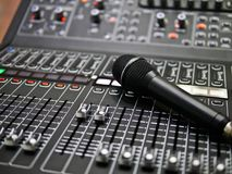 Microphone rests on an audio mixer controller in the control room, Sound mixer control for live music and studio equipment, music. Microphone rests on an audio stock photo
