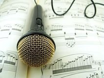 Microphone on sheet music. Microphone with wire on sheet music notes Royalty Free Stock Photos