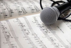 Microphone on sheet of music. Microphone and cable lying on sheet of music stock photo