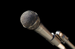 Microphone. Silver gray microphone on a stand with a black background royalty free stock photography