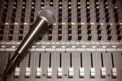Microphone on sound  mixer background. Royalty Free Stock Image