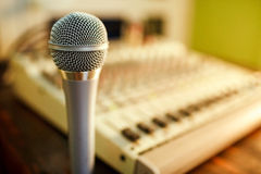 Microphone on sound mixer background. Copy space for  text. Microphone on sound mixer background, silver chrome, evening light Stock Photo