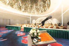 Microphone on the speech podium over the Abstract of conference. Hall or seminar room with attendee and bokeh, Business meeting concept stock photography