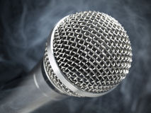 Microphone on stage. A dynamic microphone over a black and smoky background Stock Images