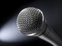 Microphone on stage. A dynamic microphone on stage. Bright spot light on the background Stock Image