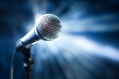 Microphone on stage. On blue background Stock Photography