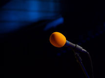 Microphone on the stage. Orange microphone on the stage and dark hall Royalty Free Stock Image