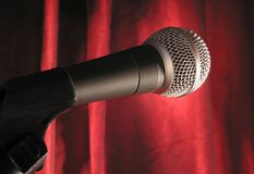 Microphone on Stage. A microphone in the spotlight with a red stage curtain Royalty Free Stock Images