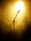 Microphone on stage. With stage-lights in the background Stock Photography