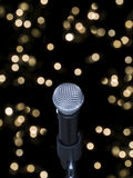 Microphone on stage. A microphone alone on stage full of out of focus lights royalty free stock photo