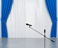 Microphone on the stage. With dark blue and silvery curtains royalty free stock photo