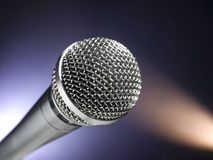 Microphone on stage. A dynamic microphone on stage. Color spot lights as background Royalty Free Stock Photos