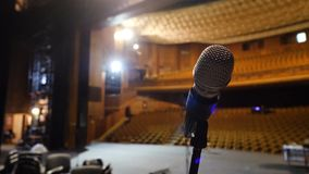 Microphone on the stage and empty hall during the rehearsal. Microphone on stage with stage-lights in the background. Microphone on the stage in the empty hall Royalty Free Stock Images