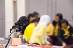 Microphone on stage with conference hall blurred background. royalty free stock photography