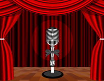 A microphone on a stage with a spotlight on it. Royalty Free Stock Images