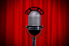 Microphone on stage with spotlight on red curtain. Retro microphone on stage against a red curtain with spotlight effect Royalty Free Stock Photography