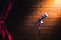 Microphone on a stage. Microphone on a stand up comedy stage with reflectors ray, high contrast image royalty free stock photo