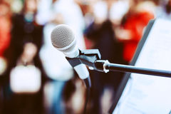 Microphone on the stand at the background of the crowd. A microphone on a stand among the colorful crowd Royalty Free Stock Photo