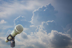 Microphone on a stand with blurred dark blue stormy clouds. Dram Stock Image