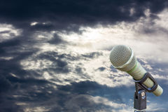 Microphone on a stand with blurred dark gray big cloud before ra Royalty Free Stock Images