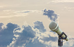 Microphone on a stand with blurred gray big cloud in the backgro Stock Image