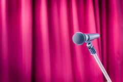 Microphone on a stand with blurred red curtain, copyspace on the royalty free stock photos