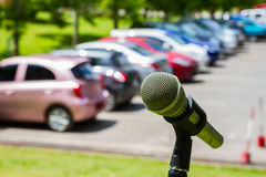 Microphone on a stand with blurred vehicles in car park backgrou Stock Images