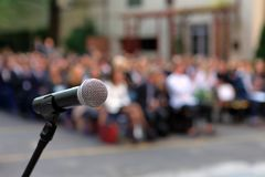 Microphone and stand in front of graduation ceremony audience ag. Ainst a background of auditorium and empty space for text royalty free stock photos
