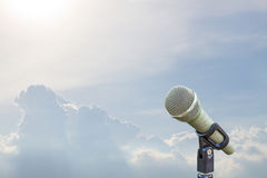 Microphone on a stand over blurred cloudy blue sky. Royalty Free Stock Images