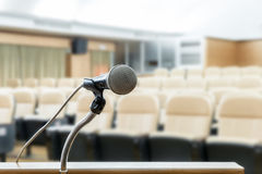 Microphone stand on podium with abstract blur photo of conference hall or seminar room in background. Business seminar concept. royalty free stock image