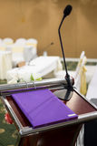 Microphone stand on podium. Book speed on podium with abstract blur photo of conference hall or seminar room in background. Business seminar concept stock images