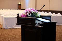 Microphone on stand podium decoration with flower. Bouquet in meeting room royalty free stock images