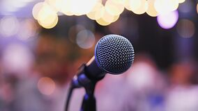 Microphone on the stand is standing on the stage. Close-up microphone on the background of the auditorium, spotlight stock footage