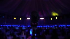 Microphone on the Stand is Standing on the Stage, Close-Up Microphone on the Background of the Auditorium,