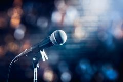 Microphone on a stage. Microphone on a stand up comedy stage with colorful bokeh , high contrast image royalty free stock photography