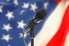 Microphone on stand with USA flag on background Stock Photography